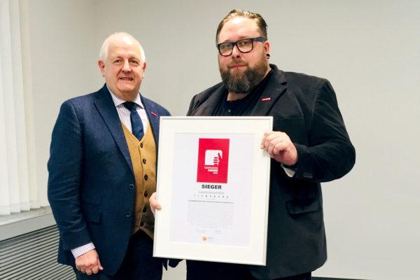 Tobias Grzesiak nahm den Kampagnen-Award 2018 von Joachim Wohlfeil (l.), Vorsitzender der AMH, entgegen. (Foto: AMH)